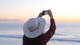 Giovane donna che prende le foto sulla spiaggia durante il tramonto o l'alba archivi video