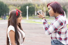 Giovane donna che prende le immagini dei suoi amici nel parco Fotografia Stock