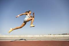 Giovane donna che prende salto in lungo Immagini Stock