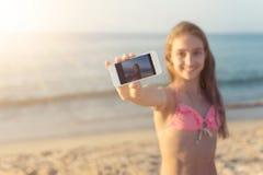 Giovane donna che prende selfie alla spiaggia sabbiosa con il mare ed all'orizzonte nei precedenti sul viaggio di giorno di estat Fotografie Stock Libere da Diritti