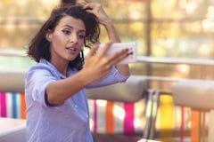 Giovane donna che prende un selfie in caffetteria fotografie stock