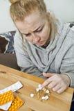 Giovane donna che prende una medicina a casa Pillole e droghe fotografia stock