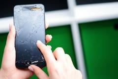 Giovane donna che prova ad utilizzare un telefono cellulare di vetro rotto Immagine Stock Libera da Diritti