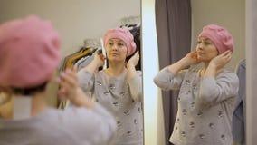 Giovane donna che prova sui vestiti La donna caucasica attraente guarda nello specchio, girando la sua testa, provante su un capp stock footage