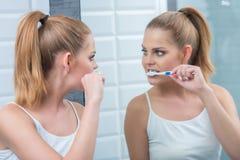 Giovane donna che pulisce i suoi denti nello specchio Immagini Stock
