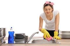 Giovane donna che pulisce un lavandino con una spugna immagini stock libere da diritti