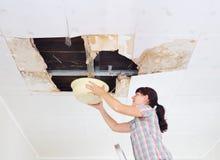Giovane donna che raccoglie acqua in bacino dal soffitto Lastra di vetro del soffitto Immagini Stock Libere da Diritti
