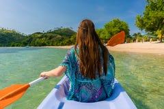 Giovane donna che rema una canoa lungo la riva di un islan idilliaco Fotografia Stock