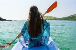 Giovane donna che rema una canoa lungo la riva di un islan idilliaco Fotografia Stock Libera da Diritti