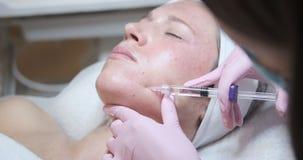 Giovane donna che riceve l'iniezione del botox nella sua guancia video d archivio