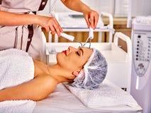 Giovane donna che riceve massaggio facciale elettrico immagine stock libera da diritti