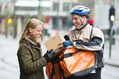 Giovane donna che riceve un pacchetto dal corriere Immagine Stock