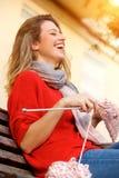 Giovane donna che ride e che tricotta maglione immagine stock libera da diritti