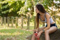 Giovane donna che riposa dal funzionamento su un tronco dell'albero Fotografia Stock Libera da Diritti