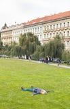 Giovane donna che riposa mettendo sull'erba in un parco della città Fotografia Stock