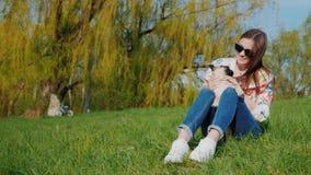 Giovane donna che riposa nel parco, sedentesi su un prato inglese verde Tiene un cucciolo sul suo rivestimento, giochi del carlin stock footage