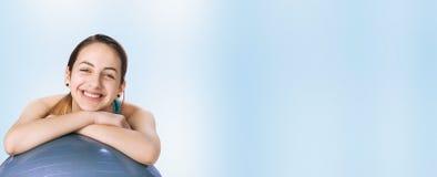 Giovane donna che riposa su una palla di forma fisica dopo l'allenamento Immagine Stock