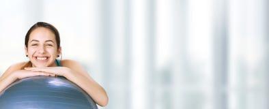 Giovane donna che riposa su una palla di forma fisica dopo l'allenamento Fotografia Stock Libera da Diritti