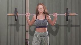 Giovane donna che risolve con un bilanciere con i pesi pesanti sulle sue spalle video d archivio