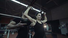 Giovane donna che risolve i pesi di sollevamento video d archivio