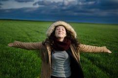 Giovane donna che ritiene felice in un campo verde con le nuvole che godono dell'aria fresca Fotografia Stock