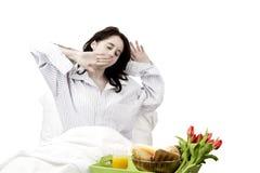 Giovane donna che sbadiglia prima della prima colazione Immagini Stock