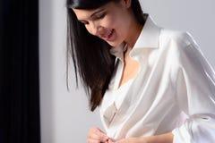 Giovane donna che sbottona la sua camicia Immagini Stock
