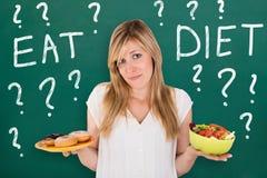 Giovane donna che sceglie alimento sano e non sano fotografia stock libera da diritti