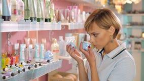 Giovane donna che sceglie crema cosmetica nel negozio di bellezza Fotografia Stock