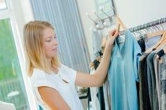 Giovane donna che sceglie indumento immagine stock libera da diritti