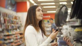 Giovane donna che sceglie padella in deposito archivi video