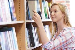Giovane donna che sceglie un libro in libreria Fotografia Stock