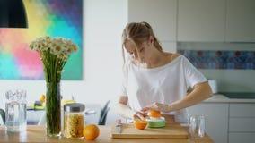 Giovane donna che schiaccia succo d'arancia fresco con lo spremitoio dell'agrume video d archivio