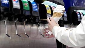 Giovane donna che seleziona acqua a partire dalla macchina della soda di self service all'area della corte di alimento di Costco video d archivio