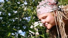 Giovane donna che sente l'odore di un fiore HD archivi video