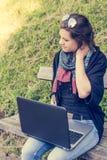 Giovane donna che sfrega il suo collo mentre lavorando ad un computer portatile Fotografie Stock