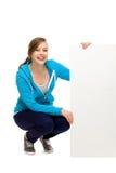 Giovane donna che si accovaccia vicino alla scheda in bianco Fotografia Stock Libera da Diritti