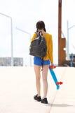 Giovane donna che si allontana con la borsa ed il pattino Immagini Stock