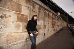 Giovane donna che si appoggia contro una parete dell'arenaria Immagini Stock