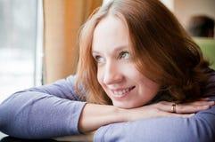 Giovane donna che si appoggia su una tabella Fotografia Stock