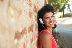Giovane donna che si appoggia un muro di mattoni che ascolta la musica Fotografia Stock