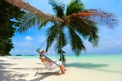 Giovane donna che si distende alla spiaggia Immagine Stock