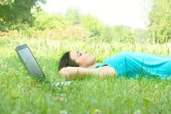 giovane donna che si distende con il computer portatile Fotografia Stock Libera da Diritti