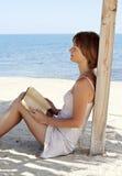 Giovane donna che si distende con un libro vicino al mare Fotografie Stock Libere da Diritti