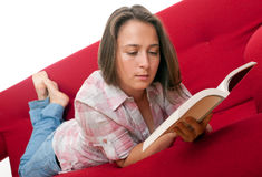 Giovane donna che si distende e che legge un libro Fotografia Stock Libera da Diritti