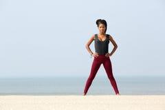 Giovane donna che si esercita alla spiaggia Immagini Stock