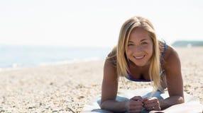 Giovane donna che si esercita alla spiaggia Fotografie Stock Libere da Diritti