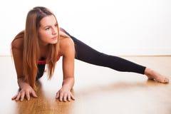 Giovane donna che si esercita - allungando Fotografia Stock
