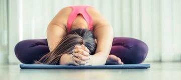 Giovane donna che si esercita allungando indietro posa di yoga Immagine Stock Libera da Diritti