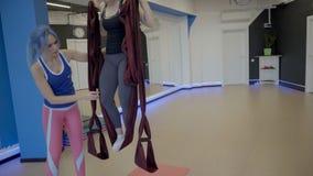 Giovane donna che si esercita in amaca con l'istruttore in studio archivi video